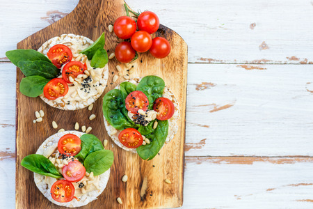 Healthy Snack from Rice Cakes with Hummus, Spinach and Tomatoes on Light Wooden Background Stock Photo
