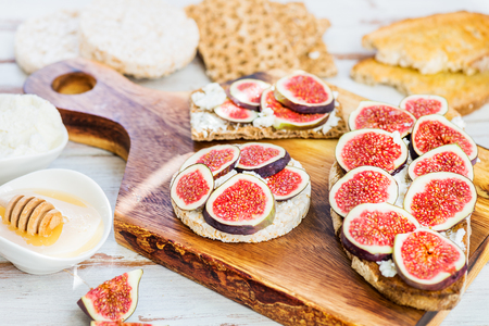 Various Healthy snacks from rice cake, wholegrain rye crispbread crackers and sourdough bread toasts together with figs and ricotta cheese on  wooden cutting board