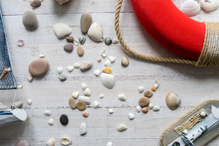 Sea theme decorations of the kids room, such as cute wooden boat, sea shells and stones, and life buoy