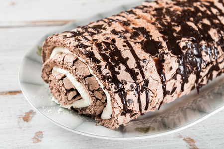 Belgian Chocolate Meringue Roulade filled with whipped cream and chocolate sauce