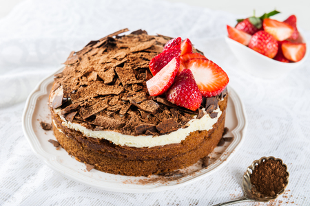 Coffee cake soaked with coffee and Marsala wine, filled and topped with mascarpone frosting and decorated with dark Belgium chocolate shavings. Strawberries and Coffee nearby on light background