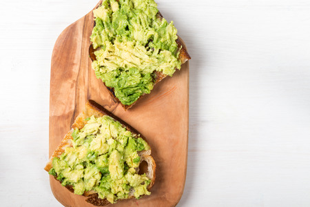 Healthy snack of avocado toasts from sourdough bread on the cutting board