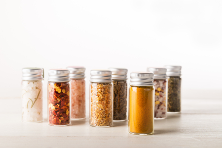 Spices Set in Mini Bottles, such as basil, turmeric, salts, chilli flakes, cumin seeds on light background  Standard-Bild