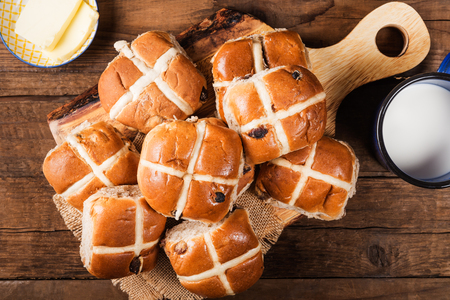 Easter Breakfast with Hot Cross Buns, served on Wooden Chopping Board, Dark wooden Rustic Background. Top View Stock Photo