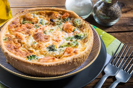 Classic salmon and broccoli quiche made from shortcrust pastry with broccoli florets and smoked salmon in a creamy free range egg custard Stock Photo