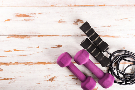 Ladies Sports Accessories such as dumbbells and skipping rope. Fitness, sport and healthy lifestyle concept. Top view, copy space