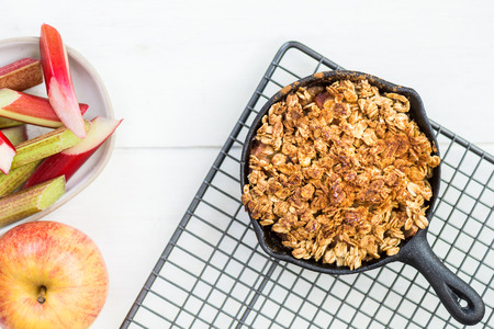 Homemade cooked rhubarb and apple crumble with oatmeal in the cast iron pans
