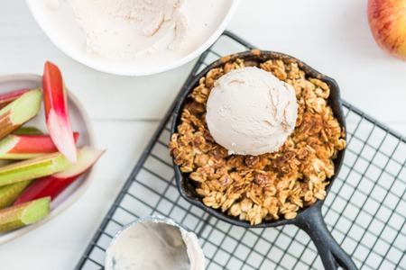 Homemade cooked rhubarb and apple crumble with oatmeal and vanilla ice cream in the iron pans