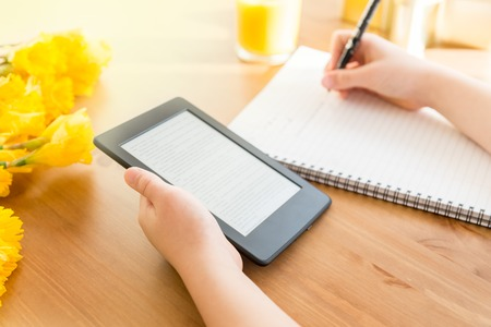 Girl is reading ebook on digital tablet device and is taking notes Stock Photo
