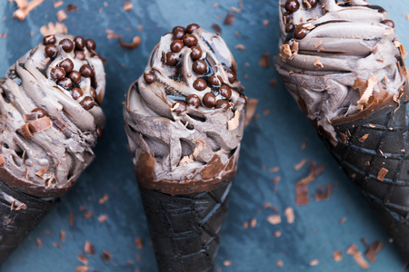 Double Chocolate Ice Creams with Black Waffle Cones on Dark Background