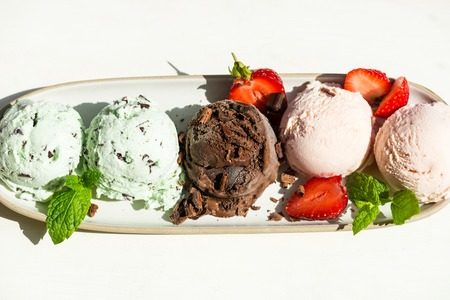 Selection of different ice cream scoops such as mint, chocolate and strawberry on the oval plate, top view Stock Photo