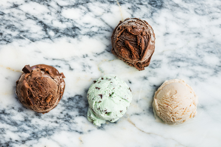 Selection of different ice cream scoops such as mint, chocolate and strawberry on marble background, top view Stock Photo