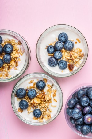 Breakfast from Fresh Natural Yogurt with Homemade Granola and Blueberries in Glass Jars on Light Pink Background Stock Photo