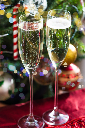Two Champagne Flutes on Christmas Background with Xmas Tree