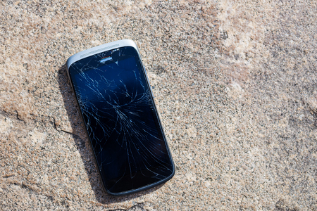 Old Black Cracked Touch Screen Phone, broken cellphone Stock Photo