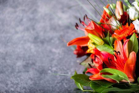 Vibrant Bouquet of different flowers such as orange Asiatic lilies, alstroemeria, germinis, yellow roses and chrysanthemums