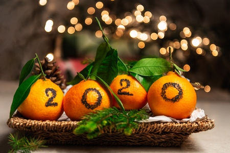 New Year 2020 is Coming Concept. Numbers written in Black Ink on the Oranges that are laying in the Basket with Pine Sticks and Xmas Lights on the Background Reklamní fotografie