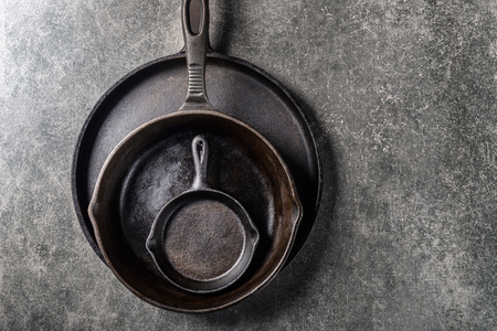 Cast iron Pans or Skillets on Grey Background Stock Photo