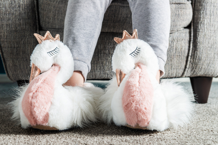 Young girl is wearing cute soft 3d swan slippers