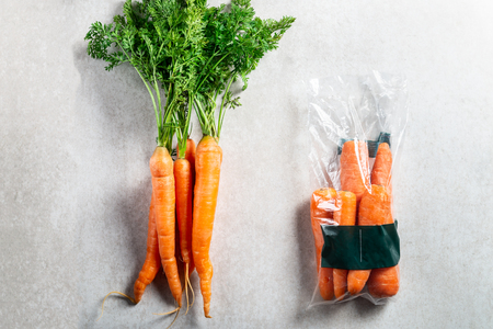 Carrots in plastic bag VS NO bag. Choose less plastic when buying vegetables. Grey background, top view, copy space