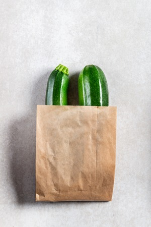 Courgettes in paper bag. Safe the planet, say no to plastic. Light grey background, top view, space for text. Reklamní fotografie