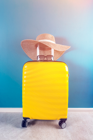 Bright and stylish cabin size suitcase with straw hat Stockfoto