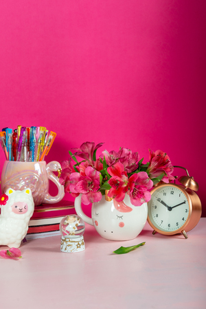 Different Notebooks, alarm clock, unicorn mug, llama squishy, Alstroemeria flowers and flamingo mug with colorful gel pens on bright pink background. Idea of Girly Desk table. Back to school concept