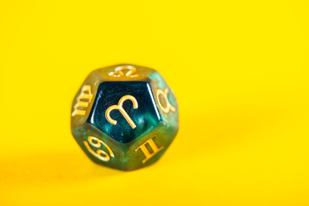 Astrology Dice with zodiac symbol of Aries Mar 21 - Apr 19 on bright yellow background