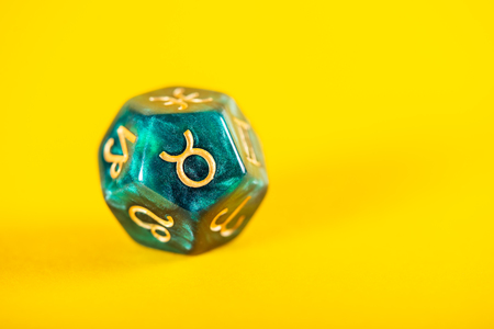 Astrology Dice with zodiac symbol of Taurus Apr 20 - May 20 on Bright Yellow Background