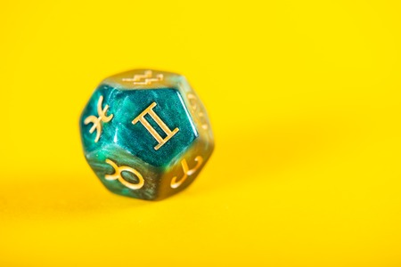 Astrology Dice with zodiac symbol of Gemini May 21 - Jun 20 on Yellow Background