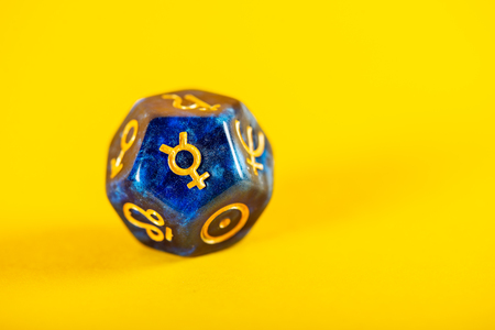 Astrology Dice with symbol of the planet Mercury on Yellow Background Imagens