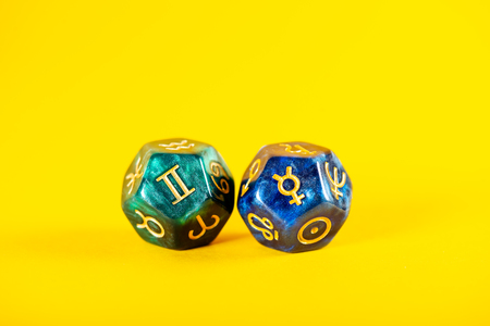 Astrology Dice with zodiac symbol of Gemini May 21 - Jun 20 and its ruling planet Mercury on Yellow Background Imagens