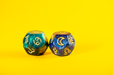 Astrology Dice with zodiac symbol of Cancer Jun 21 - Jul 22 and its ruling celestial body the Moon on Yellow Background