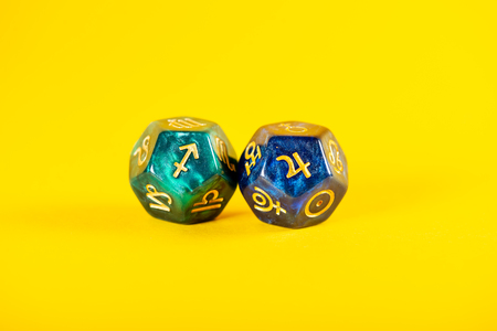 Astrology Dice with zodiac symbol of Sagittarius Nov 22 - Dec 21 and its ruling planet Jupiter on Yellow Background