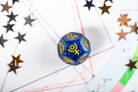 Dados de astrología con el símbolo del planeta Plutón en el fondo de la carta natal