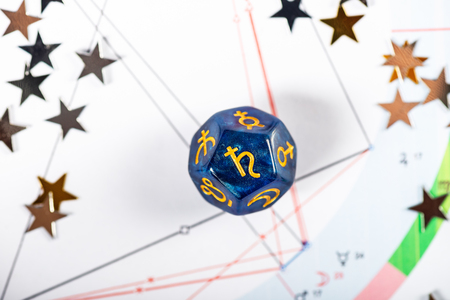 Astrology Dice with symbol of the planet Saturn on Natal Chart Background