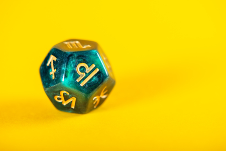 Astrology Dice with zodiac symbol of Libra Sep 23 - Oct 22 on Yellow Background