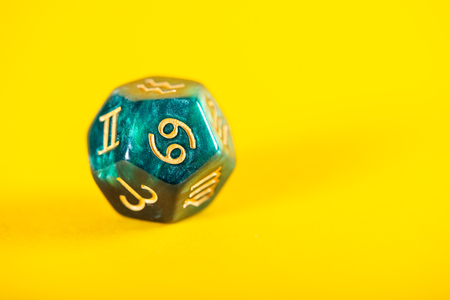 Astrology Dice with zodiac symbol of Cancer Jun 21 - Jul 22 on Yellow Background