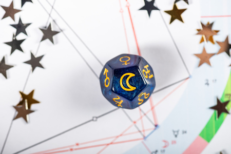 Astrology Dice with symbol of the Moon on Natal Chart Background Stock Photo