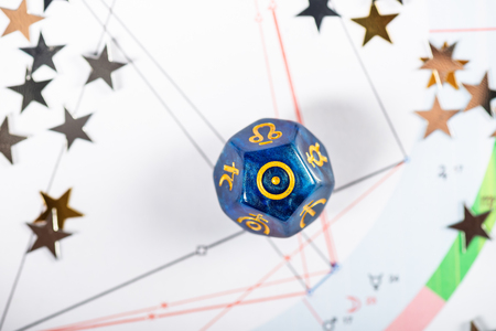 Astrology Dice with symbol of the Sun on Natal Chart Background