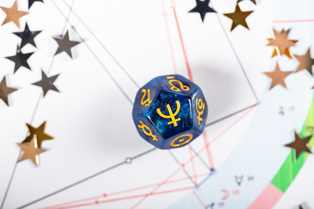 Astrology Dice with symbol of the planet Neptune on Natal Chart Background Stock Photo