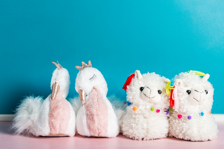 Cute soft 3d llama and swan slippers on the pink and blue background