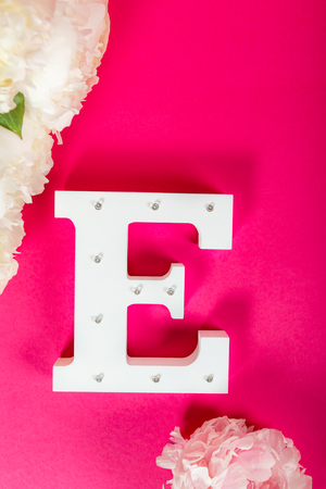 Wooden decorative letter E on pink background