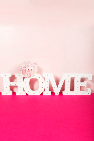 Word HOME from the wooden decorative letters on pink background