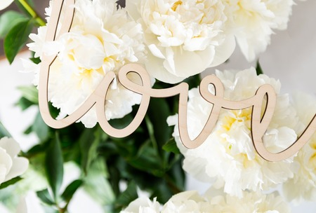 Bunch of amazing peonies in the vase and vintage letters LOVE on white wall background
