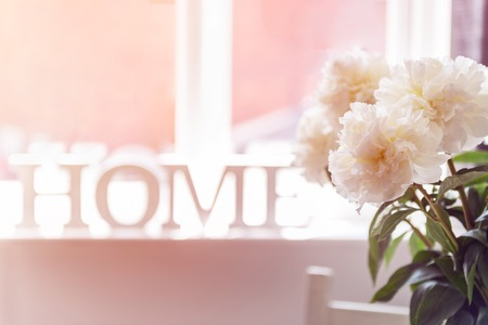 Bunch of amazing peonies in the vase and wooden letters HOME on the window