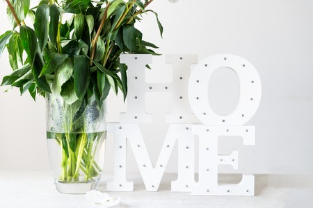 Bunch of amazing peonies in the vase and wooden letters HOME with white wall background