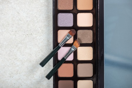 Neutral color eye shadows palette with brushes on grey background