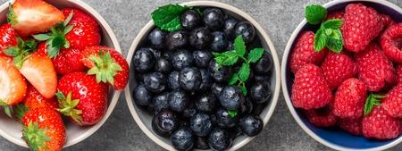 Fresh summer berries in the bowls. Blueberries, strawberries, raspberries shoot from the top