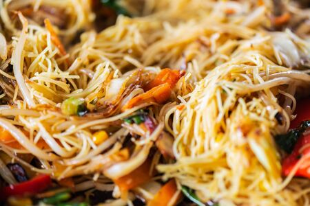 Process of cooking of sweet and crunchy stir fry with beansprouts and noodles in the wok, Macro image Stock Photo